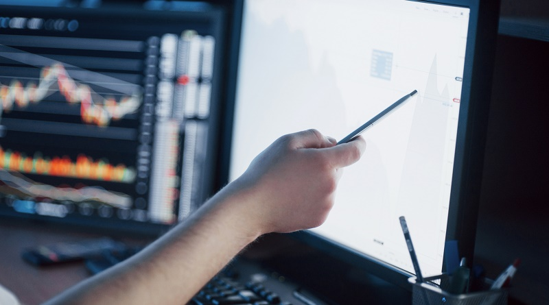 Analyzing data. Close-up of young businessman pointing on the data presented in the chart with pen while working in creative office